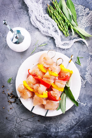 raw chicken kebab with pepper on the plate