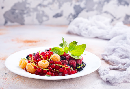 mix berries on plate and on a table Stock Photo