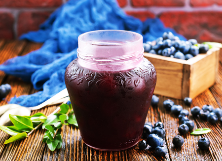blueberry jam in glass bank and on a table