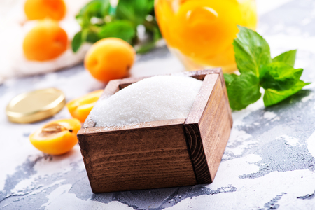 sugar and apricots on a table, ingredients for cooking jam