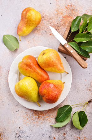old styled: fresh pears on plate and on a table