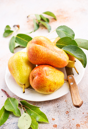 old desk: fresh pears on plate and on a table
