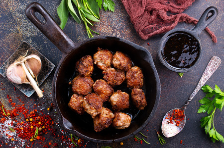fried meat malls in pan and on a table