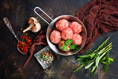 raw meatballs with salt and spice on a table