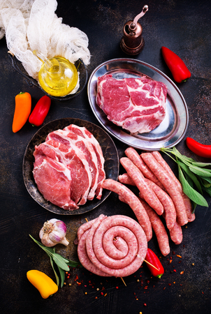 raw meat and sausages on a table, stock photo