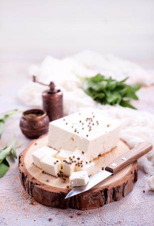 queso a bordo y sobre una mesa, foto de stock Foto de archivo
