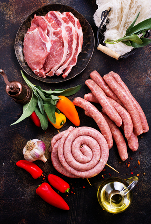 Carne cruda y salchichas en una mesa, stock photo Foto de archivo - 85540431