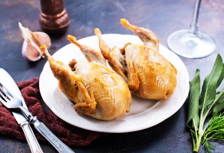 codorniz frita con especias en el plato y sobre una mesa