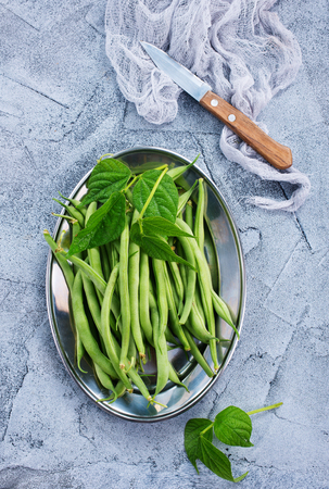 green beans on metal plate and on a table Stock Photo