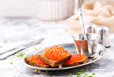 bread with red salmon caviar on metal plate Stock Photo