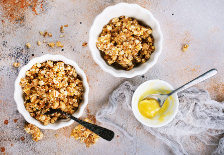 granola with honey in bowl and on a table