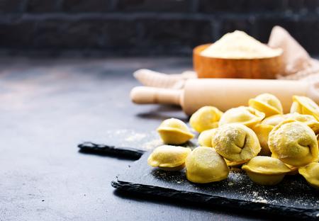raw dumplings on board and on a table Zdjęcie Seryjne - 90077783
