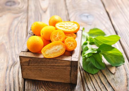 Close-up van sommige kumquat fruit in houten kom