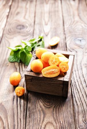 closeup of some kumquat fruits in wooden bowl Stock Photo