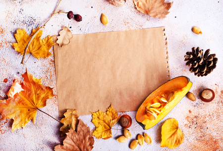 autumn background, dry leaves and paper on a table, stock photo