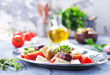 Griechischer Salat auf Teller und auf einem Tisch Standard-Bild - 90767075