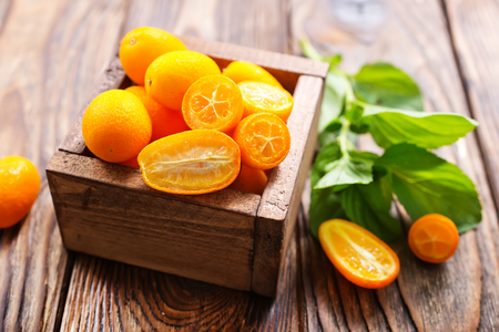 closeup of some kumquat fruits in wooden bowl Banco de Imagens
