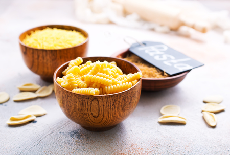 raw pasta in bowls and on a table Stock Photo