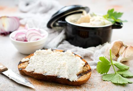 ガーリックたっぷりのラードは、素朴な白いテーブルで焼きたてのパンを提供しています。 写真素材