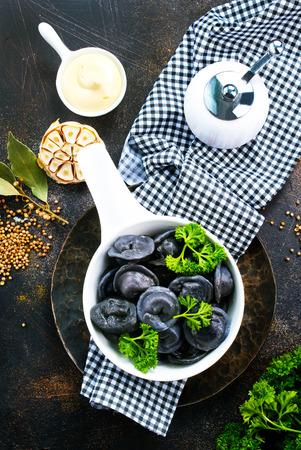 Creative dumplings from black dough, boiled pelmeni 스톡 콘텐츠
