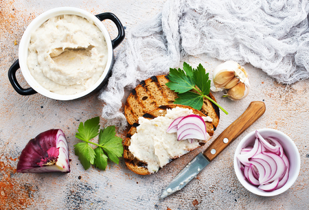 Hearty lard with garlic served with fresh bread on a rustic white table.