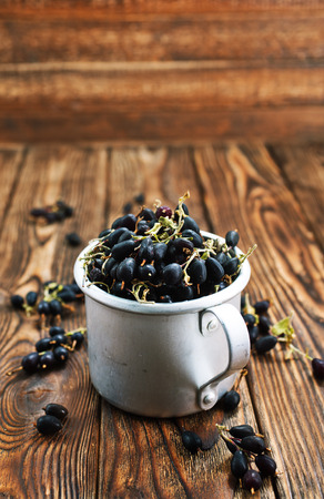 black currant in metal cup and on a table Stock Photo