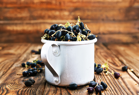 black currant in metal cup and on a table Stok Fotoğraf