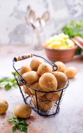raw potato in metal basket and on a table
