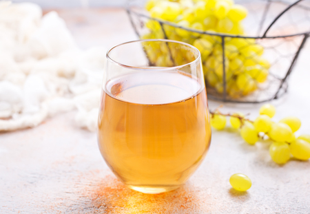 wine in glass and fresh grape on a table Stock Photo