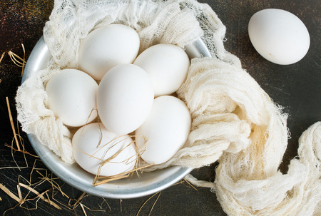 raw eggs on pkate and on a table, stock photo Stock Photo