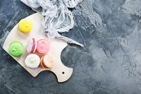 color macaroons on board and on a table Stock Photo
