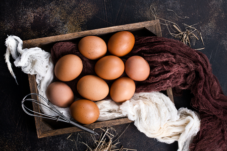 raw eggs in metal basket and on a table Stock Photo
