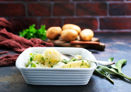 boiled potato in white bowl and on a table Stock Photo