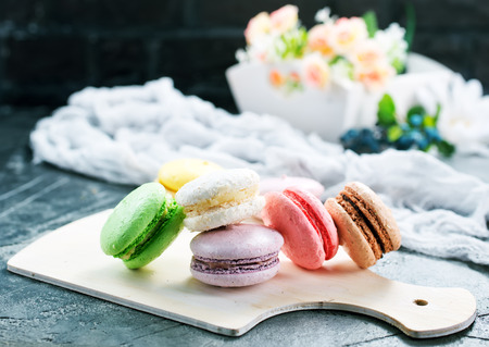 color macaroons on board and on a table Imagens