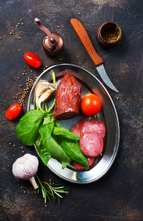 smoked sausage with spice and fresh basil Stock Photo