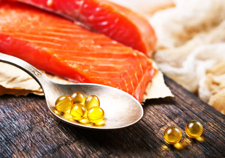 Fish oil capsules with omega 3 on wooden board