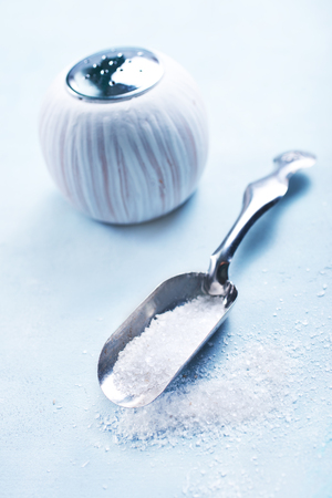 sea salt in metal spoon and on a table