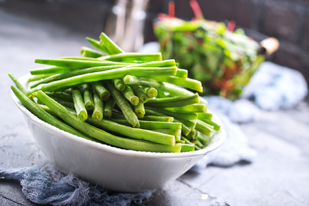 green beans in bowl and fresh leaves of mangold