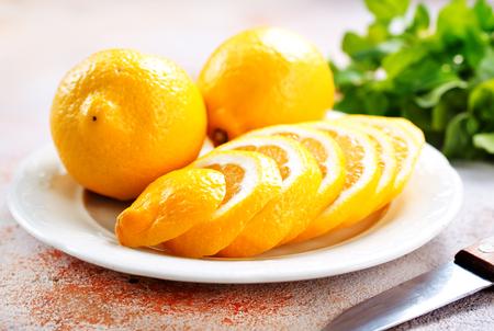 Fresh lemons and lemon slice on metal plate