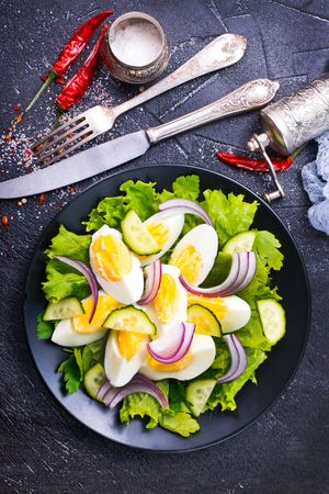 salad with boiled eggs on black plate
