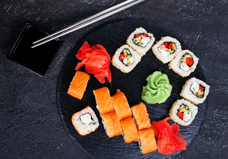 Japanese sushi on a rustic dark background. Sushi rolls and ginger, wasabi, soy sauce.