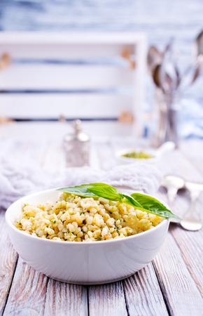 boiled bulgur with sauce Pesto in white bowl