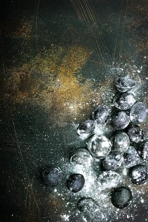 black pelmeni on wooden board, raw pelmeni