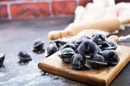 black pelmeni on wooden board, black pelmeni