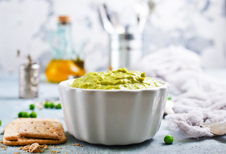 Mashed green peas and olive oil in a ceramic bowl on a table.