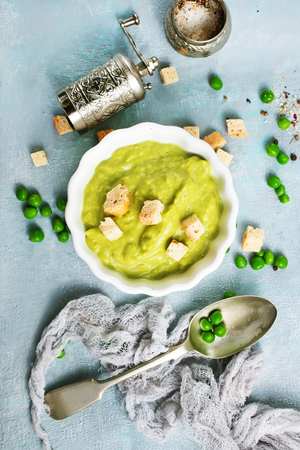 Mashed green peas and olive oil in a ceramic bowl on a table. Healthy vegetarian food Stock Photo