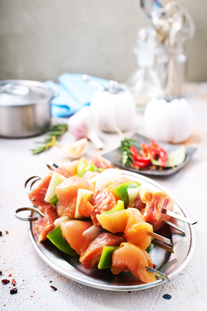 raw kebab with vegetables on metal plate