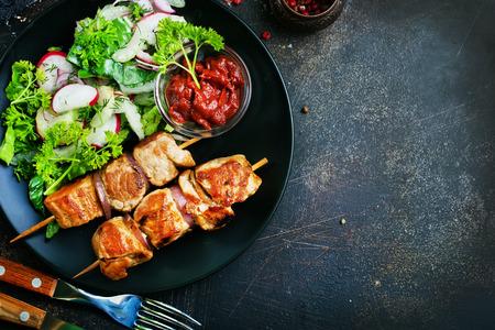 kebab and vegetable salad on plate.