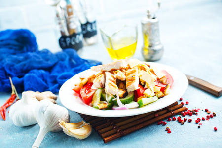 salad with fresh vegetables and baked chicken fillet Imagens