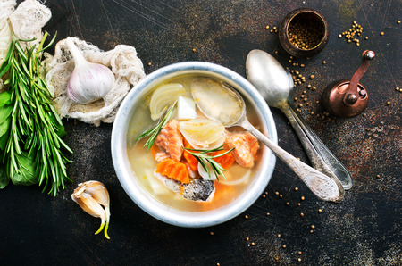 fish soup in bowl, fresh soup with salmon and greens